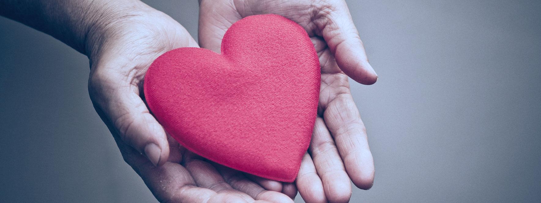 Mains tenant un coeur signe de fidélisation de sa clientèle