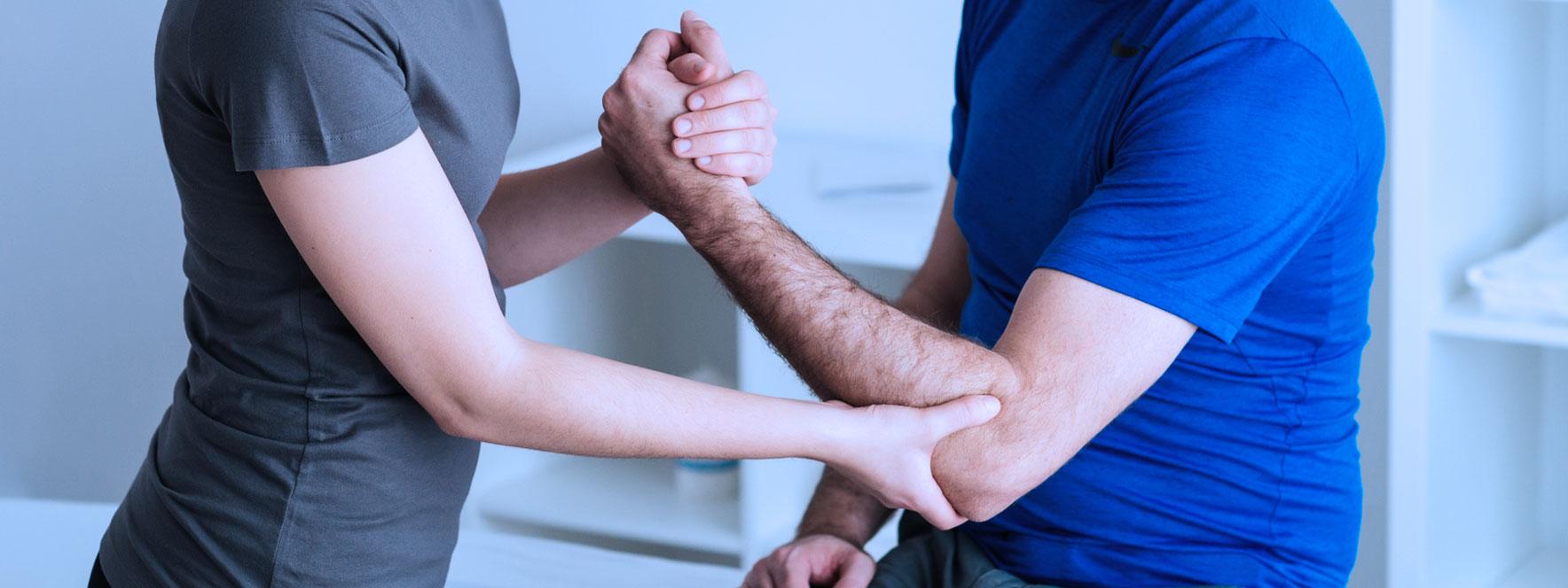 Homme se fait masser le coude les LATR par l'orthothérapie