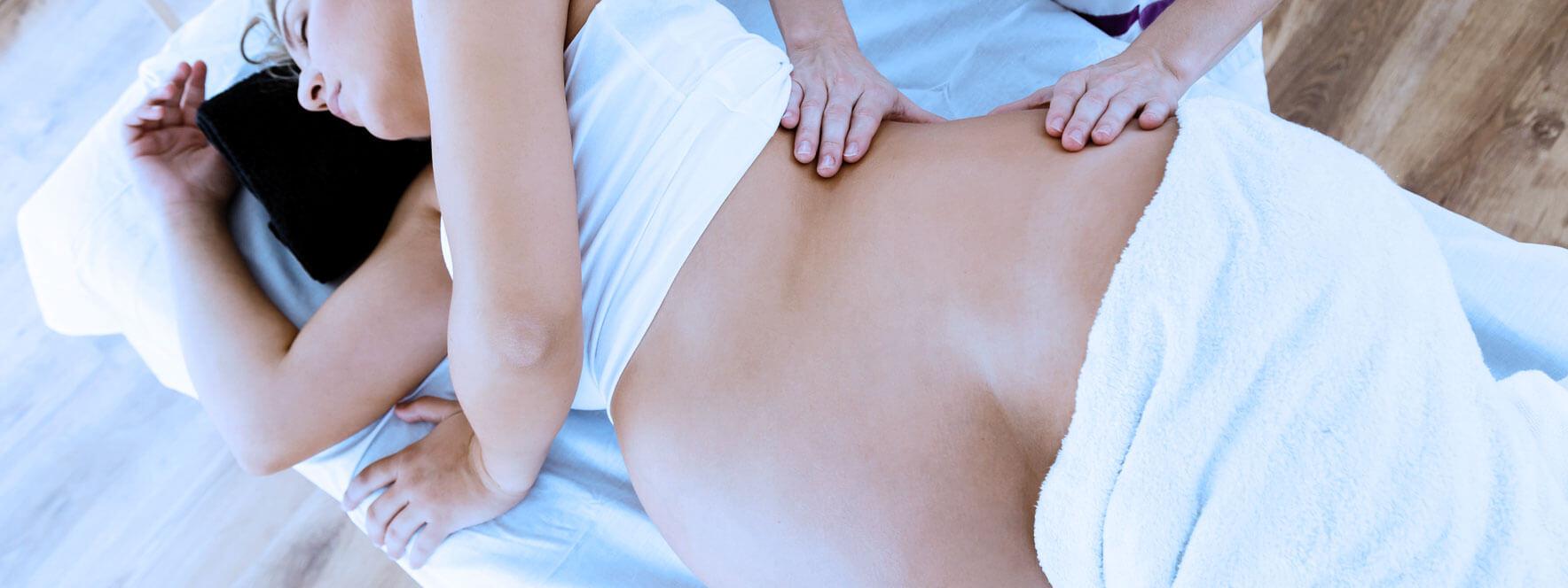 Femme enceinte qui reçoit un soin en massothérapie