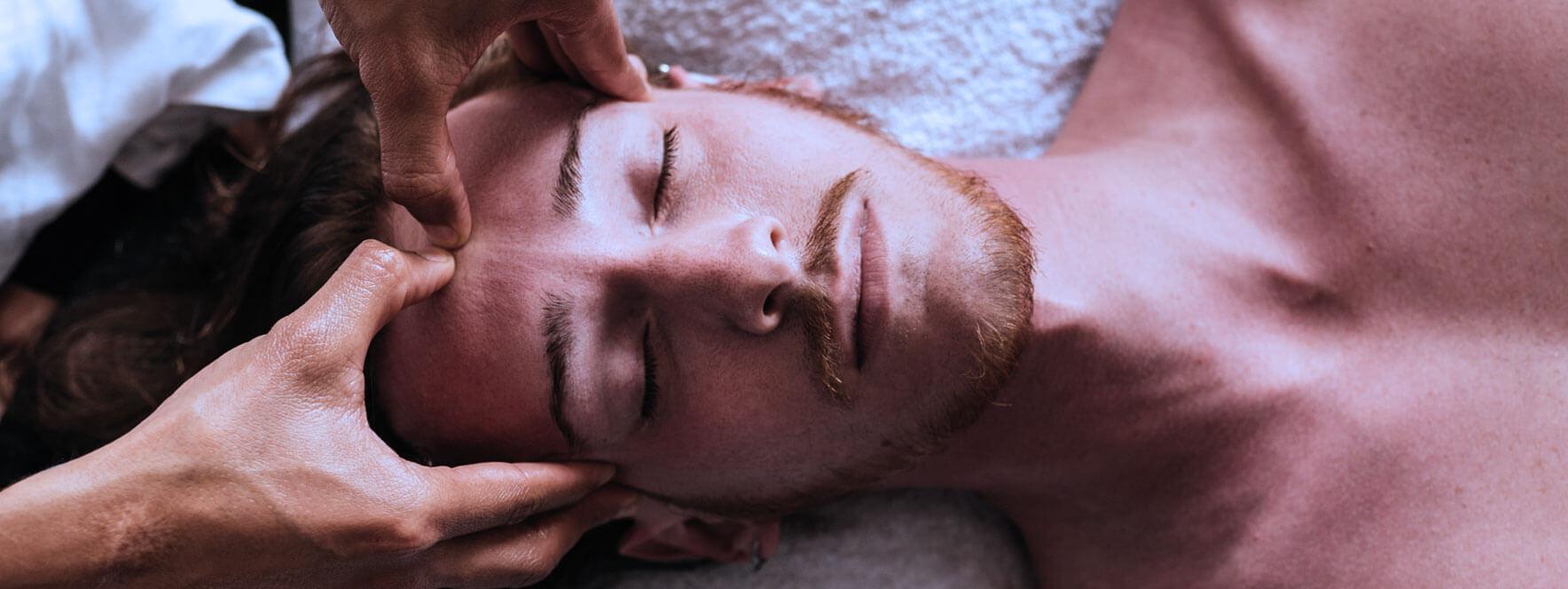 Jeune homme recevant un massage de la tête